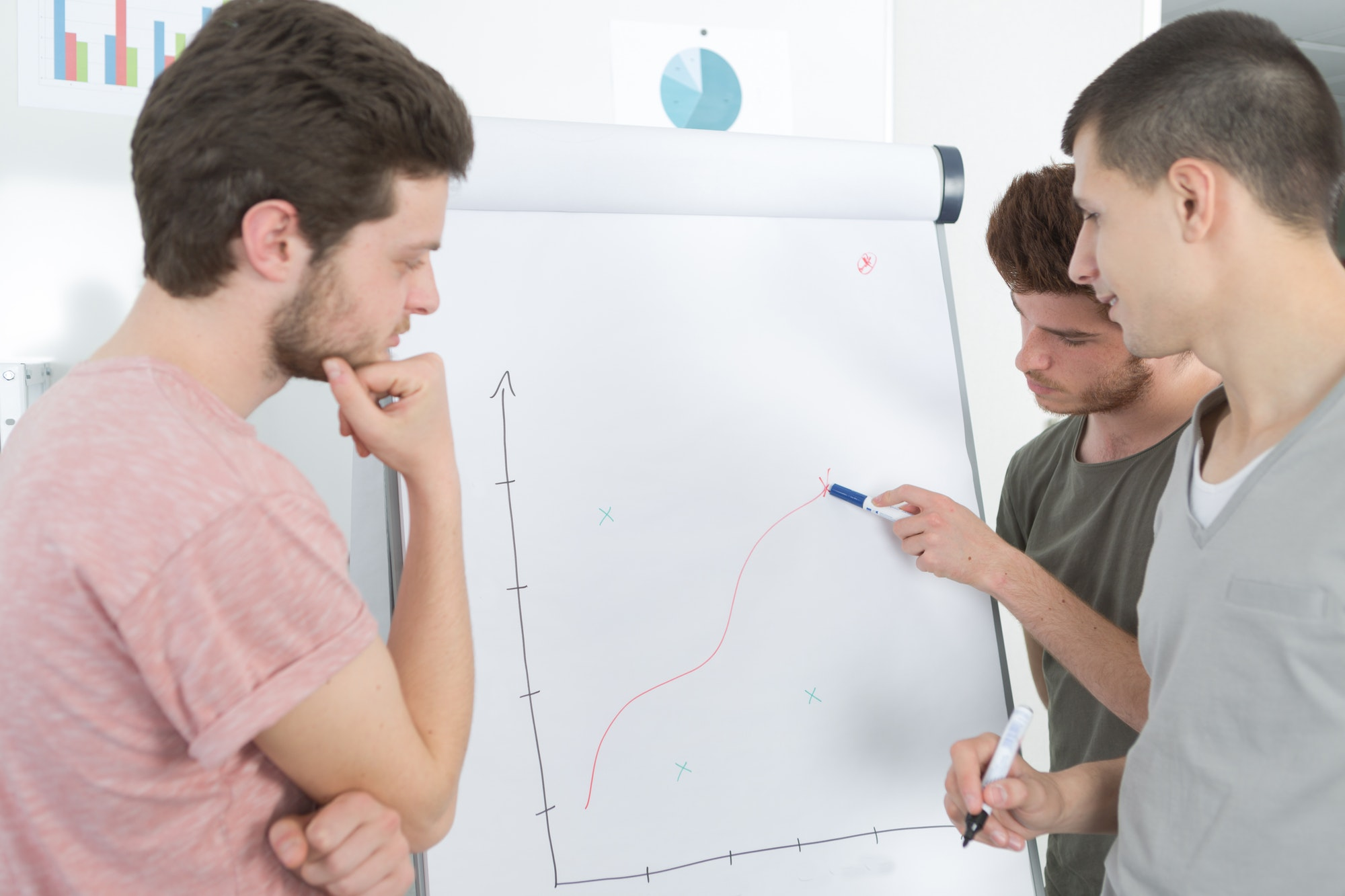 Young men tracing graph on flip chart